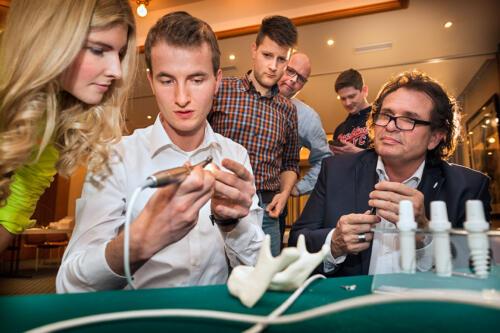 Unter Anleitung von Rene Trenkle probieren die Teilnehmer das Setzen von Zirkonimplantaten aus. Foto Dietrich Hackenberg